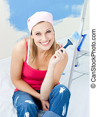 Joyful young woman holding a paint brush smiling at the camera