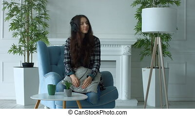 Joyful young woman in headphones enjoying music