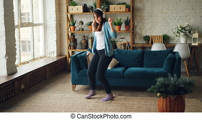 Joyful young woman is dancing at home listening to music...