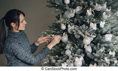 Joyful young woman is decorating New Year tree with stylish silver balls and golden lights enjoying festive activity in December. People and traditions concept.