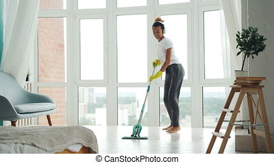 Joyful young woman is enjoying music in headphones, dancing and singing during routine cleanup at home, girl is mopping floor and having fun. People and houses concept.