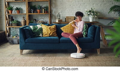 Joyful young woman is playing with robotic vacuum cleaner...
