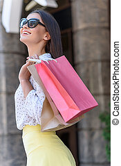 Joyful young woman is satisfied with purchase
