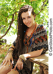 Joyful young woman portrait with dreadlocks dressed in boho style dress and necklace, sunny outdoor
