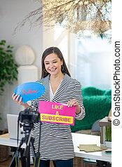 Joyful young woman promoting her video blog