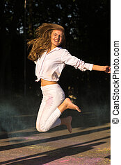 Joyful young woman with long hair jumping in the park