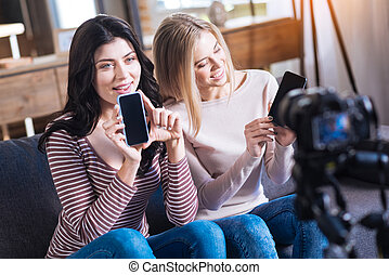 Joyful young women showing their smartphones
