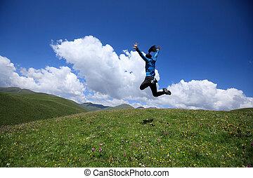joyfully woman jumping on mountain top grassland