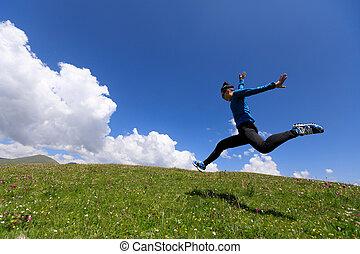 joyfully woman running jumping on mountain grassland