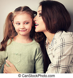 Joying young mother whispering the secret to her funny grimacing daughter in ear in studio. Toned closeup portrait