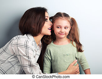 Joying young mother whispering the secret to her funny grimacing daughter in ear in studio