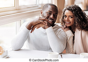 Joyous African American couple sitting in the cafe