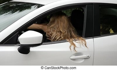 joyous attractive woman looking at car side mirror and...