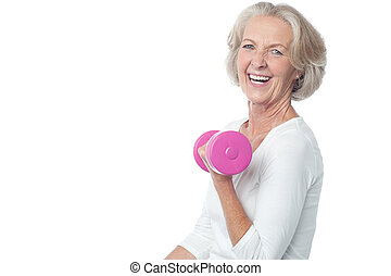Joyous fit woman lifting dumbbells - Senior woman in gym...