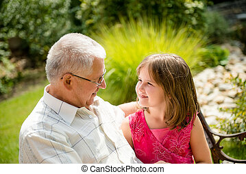Portrait of grandchild with grandfather - outdoor in backyard