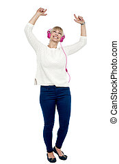 Joyous middle aged woman dancing to the beat, full length portrait.