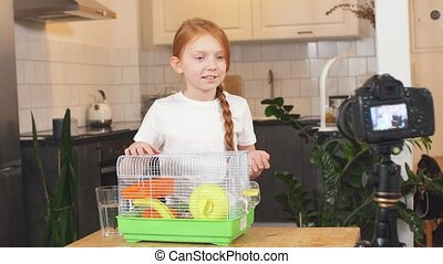 joyous red-haired girl holding a rodent cage shows it to the camera, a teen blogger. A long-awaited gift