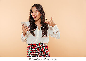 Joyous woman pointing finger on her smartphone being glad to use modern electronic device over beige background