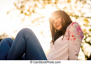 Young woman sitting outdoor and enjoying life with sun in background