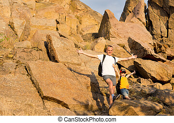 Jubilant father and son on a mountainside