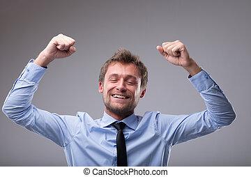 Jubilant happy man cheering and punching the air