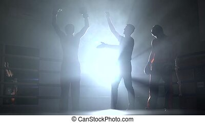 Judge at the kickboxing competitions announces the winner in sparring. Smoke background. Light from behind. Silhouette