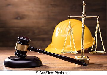 Gavel In Front Of Yellow Safety Helmet And Golden Scale -...