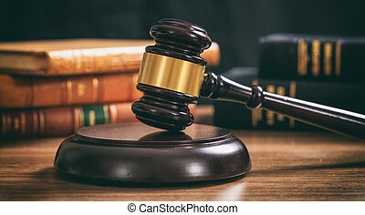 Judge gavel on a wooden desk, law books background