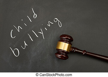 "Judge gavel on blackboard background writing the word ""child bullying""."