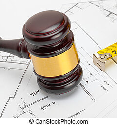 Judge gavel with measure tape above construction blueprin