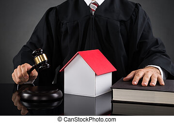Judge Holding Gavel With House Model