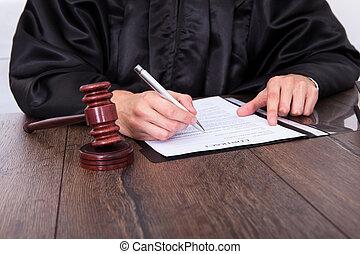 Close-up Of A Judge Hitting Mallet At Desk