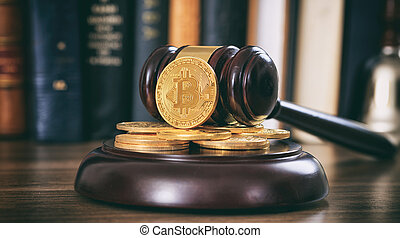 Judge or auction gavel and bitcoins on a wooden desk
