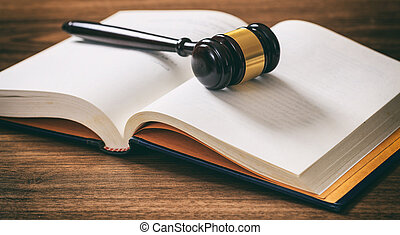 Judge or auction gavel on an open book, wooden desk