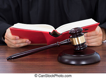 Judge Reading Law Book At Desk