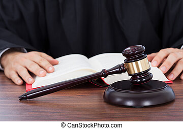 Judge Reading Law Book At Desk - Closeup of gavel placed on...