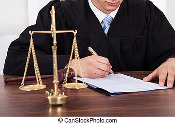 Judge Signing Document At Table In Courtroom - Midsection of...