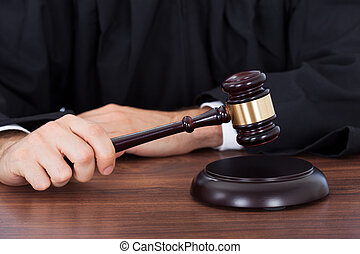 Judge Striking Gavel On Block At Desk - Midsection of male...