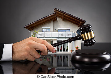 Judge With House Model Hitting Gavel