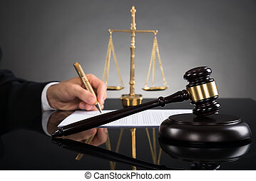 Judge Writing On Paper At Desk