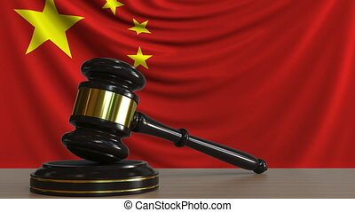 Judge's gavel and block against the flag of China. Chinese...