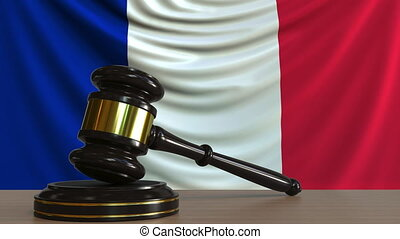 Judge's gavel and block against the flag of France. French...