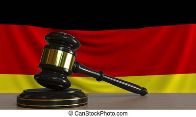 Judge's gavel and block against the flag of Germany. German...