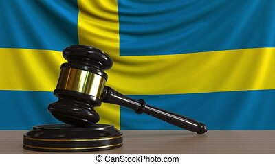 Judge's gavel and block against the flag of Sweden. Swedish...