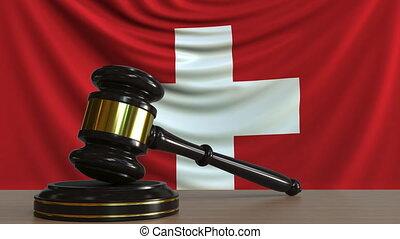 Judge's gavel and block against the flag of Switzerland....