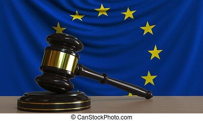 Judge's gavel and block against the flag of the European...