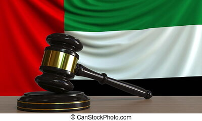 Judge's gavel and block against the flag of the United Arab...