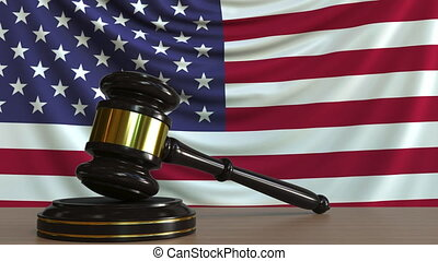 Judge's gavel and block against the flag of the United...