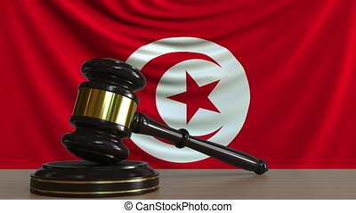 Judge's gavel and block against the flag of Tunisia....