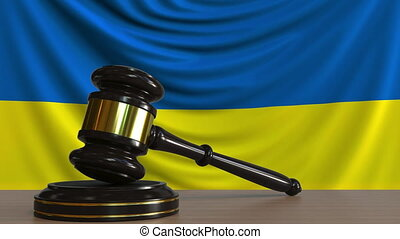 Judge's gavel and block against the flag of Ukraine....